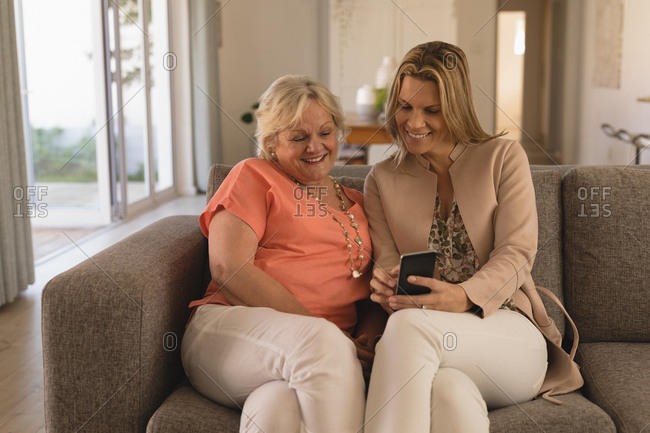 Mother and daughter using mobile phone in living room at home