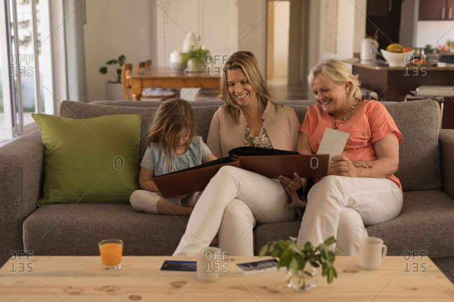 Multi-generation family looking at photo album in living room at home