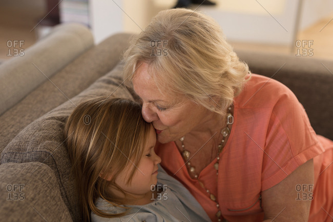 Grandmother kissing her granddaughter in living room at home