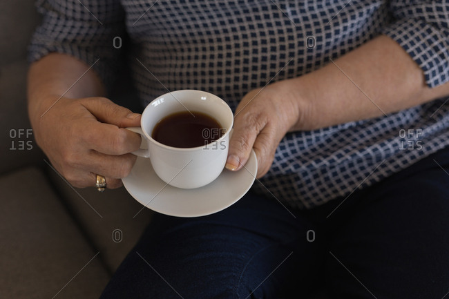 Mid section of senior woman having black coffee in living room at home
