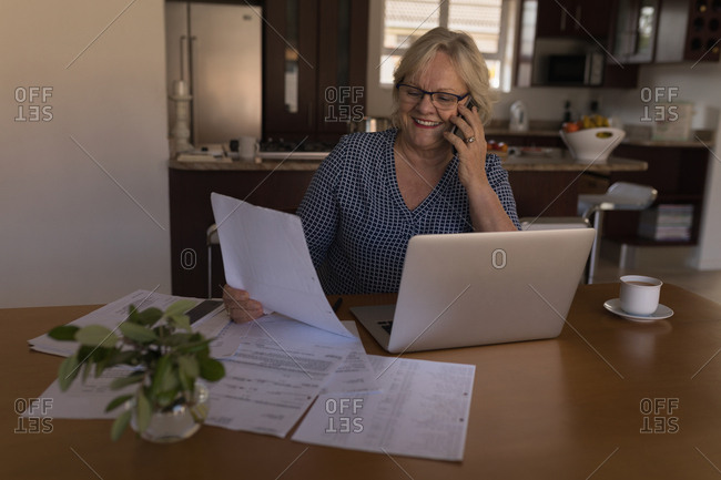 Senior woman talking on mobile phone while looking at document at home