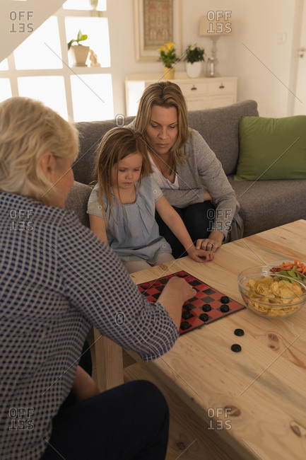 Multi-generation family playing game in living room at home