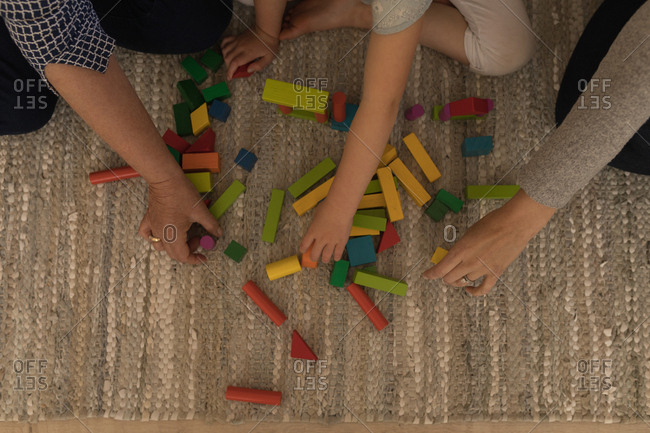 Multi-generation family playing with building blocks in living room at home