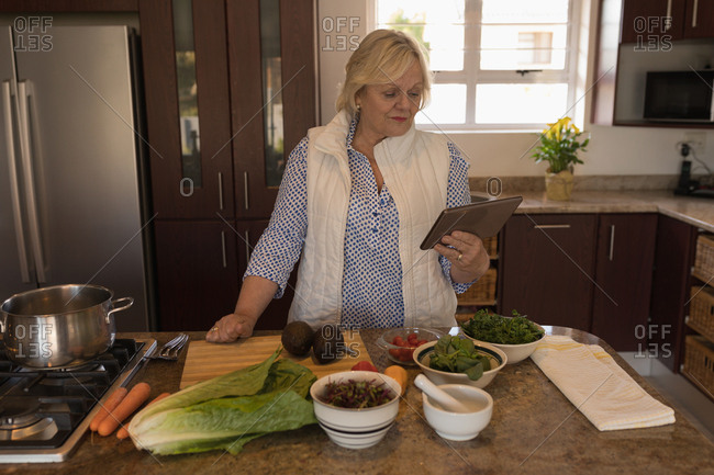 Senior woman looking recipe on digital tablet in kitchen at home