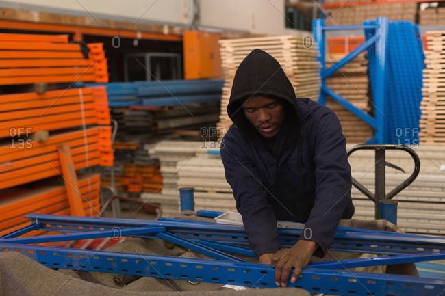 Worker arranging pallet rack at rope making industry