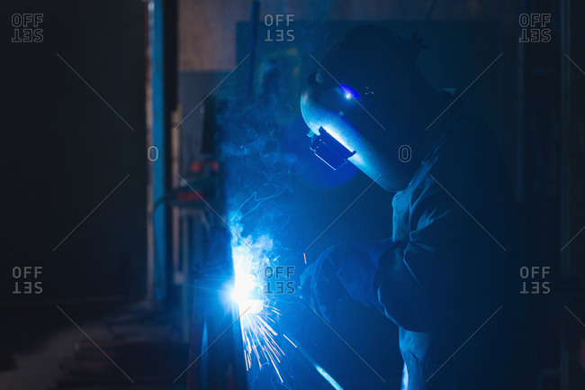 Attentive worker using welding torch in rope making industry