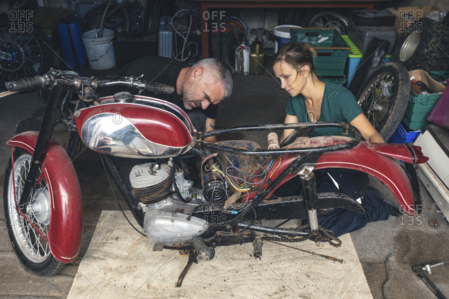 Mechanic repairing motorbike in repair garage