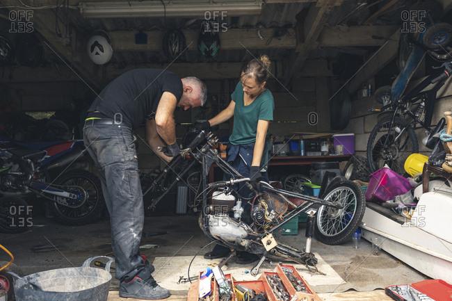 Mechanic repairing motorbike in repair garage