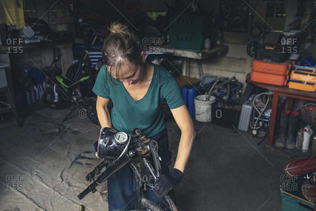 Female mechanic repairing motorbike in repair garage