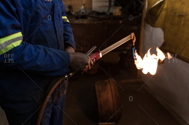 Mid section of blacksmith using a welding torch in workshop