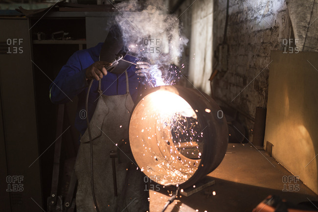 Attentive blacksmith using a welding torch in workshop