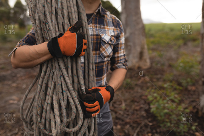 Mid section of lumberjack holding rope in forest