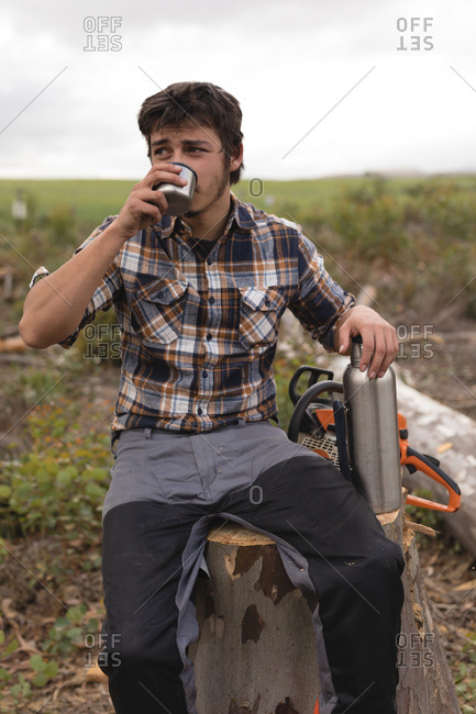 Lumberjack having a water while relaxing on tree stump in the forest