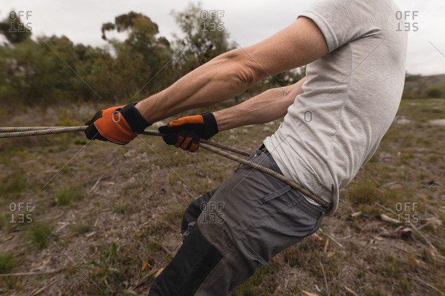 Mid section lumberjack pulling rope in the forest