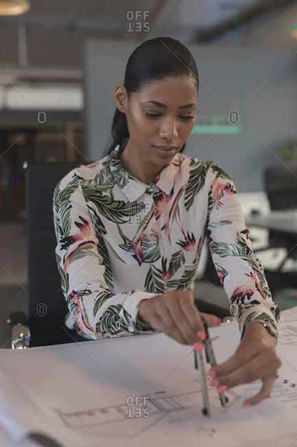 Female executive drawing on blueprint at desk in office