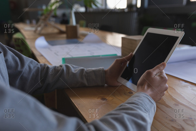 Mid section of male executive using digital tablet in office