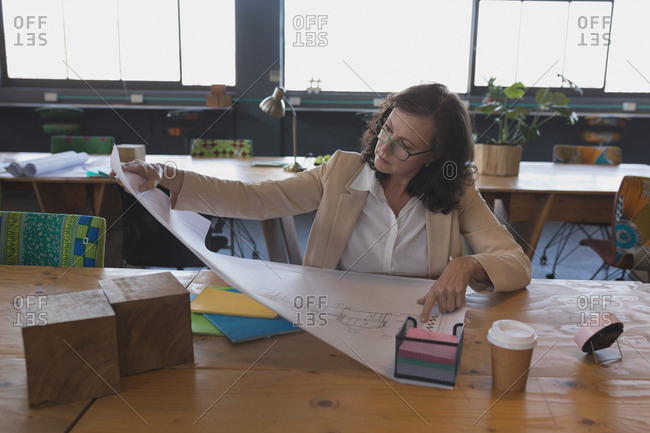 Female executive working on blueprint at table in office