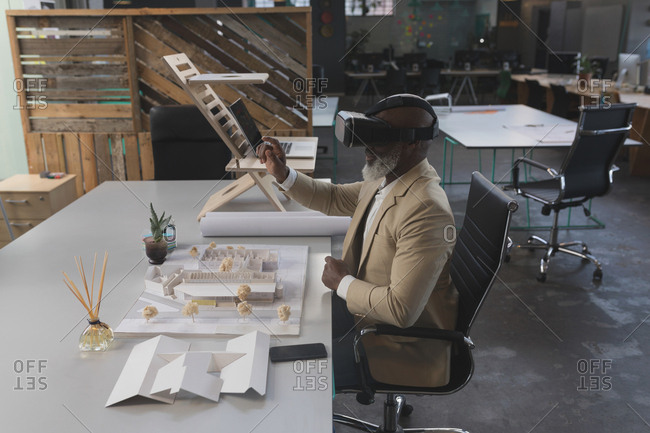 Male executive using virtual reality headset at table in office
