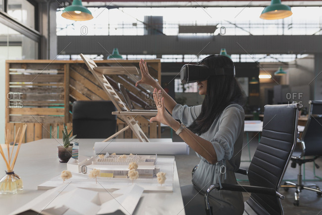 Female executive using virtual reality headset at table in office