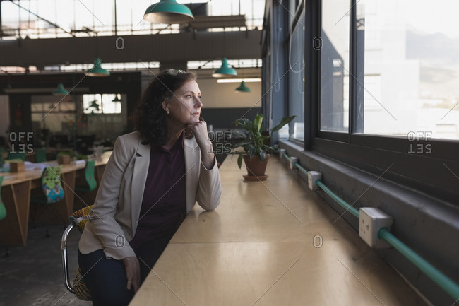 Thoughtful woman looking through window in office