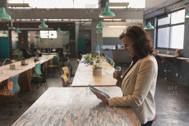 Female executive using digital tablet at table in office