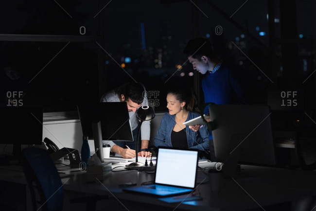 Three business people working on laptop in office during nighttime