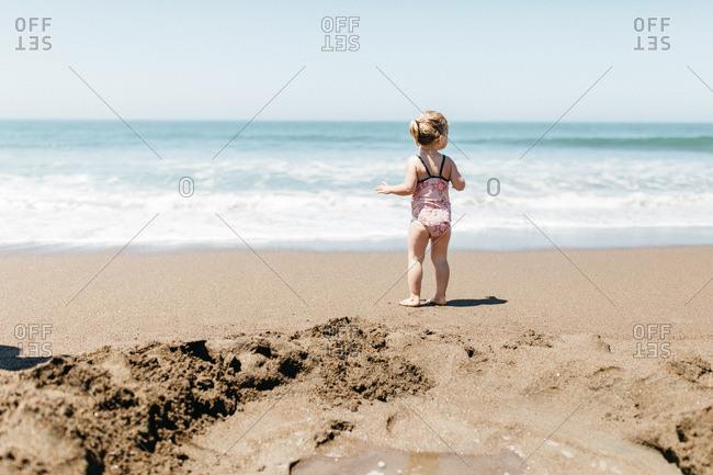 Blonde toddler girl on Rodeo Beach, California