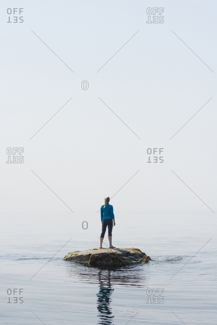 Woman on a rock surrounded by water in the Strait of Georgia, southern coastal British Columbia, Canada