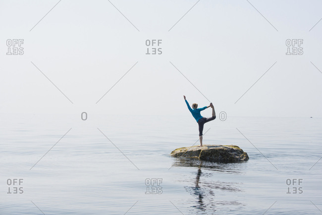 Woman doing yoga pose on a rock surrounded by water in the Strait of Georgia, southern coastal British Columbia, Canada