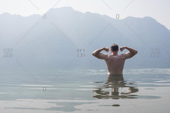 Man flexing while swimming in Desolation Sound, southern coastal British Columbia, Canada