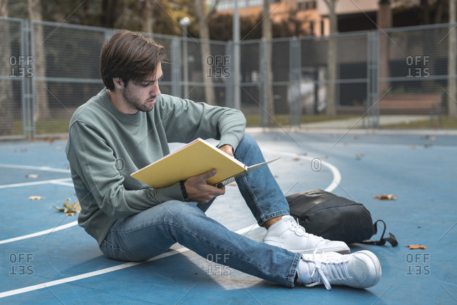 Young man reading a notebook seated on blue basketball court of campus