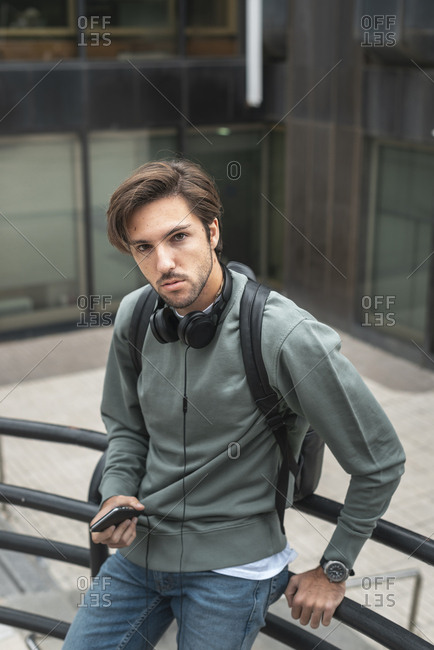 Portrait of young man with phone on stairs of campus wearing headphones and a black backpack