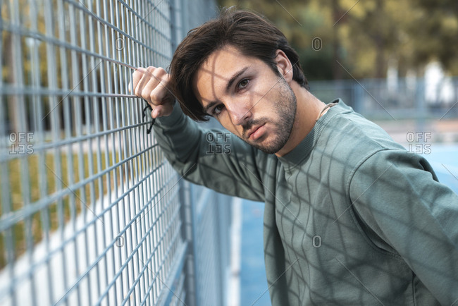 Portrait of young handsome man leaning on fence of basketball court