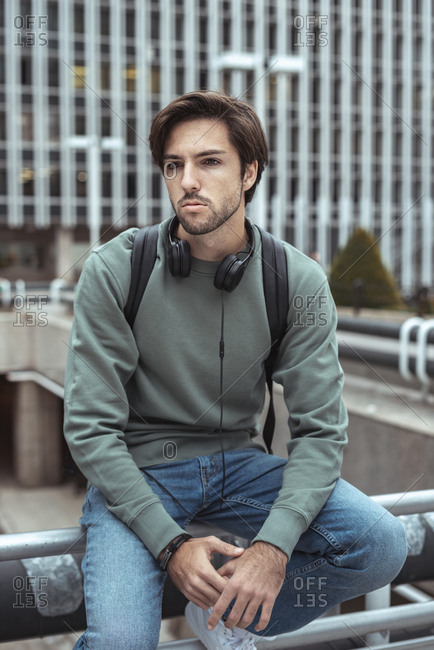 Portrait of young man looking away seated on railing of campus wearing headphones and a black backpack