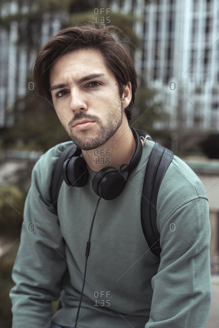 Portrait of young man looking at camera on campus wearing headphones and a black backpack