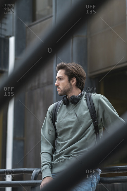 Portrait of young man looking away on stairs of campus wearing headphones and a black backpack