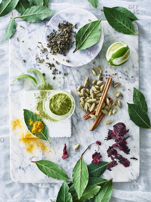 Tea and other herbs on marble cutting surface