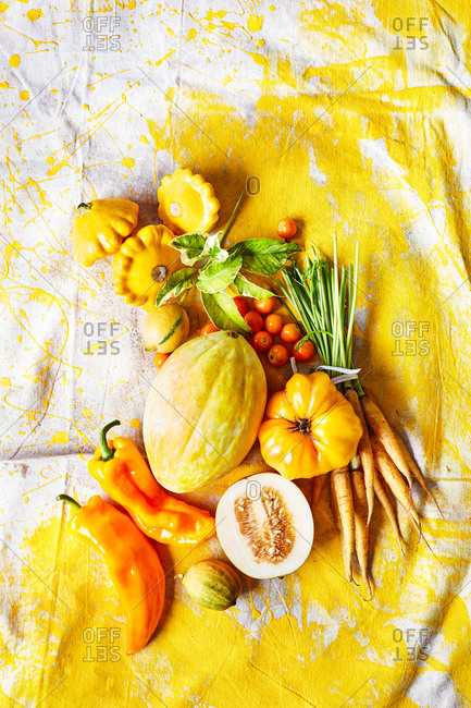 Yellow fruit and veggies on white and yellow background