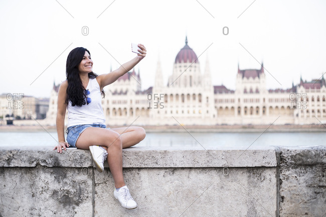 Woman taking a selfie sitting on a wall with Hungarian Parliament in background, Budapest, Hungary