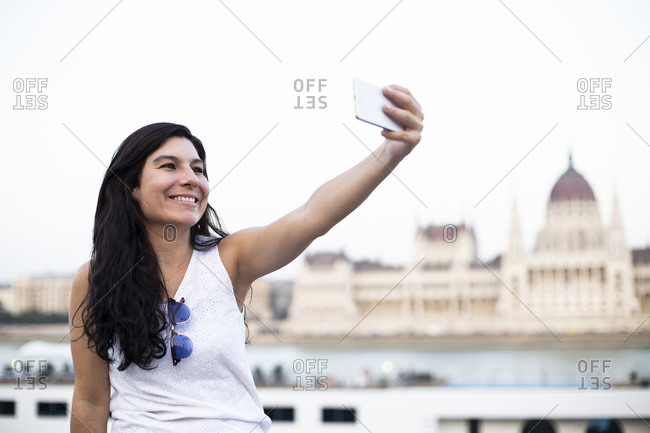 Beautiful woman taking a selfie sitting on a wall with Hungarian Parliament in background, Budapest, Hungary