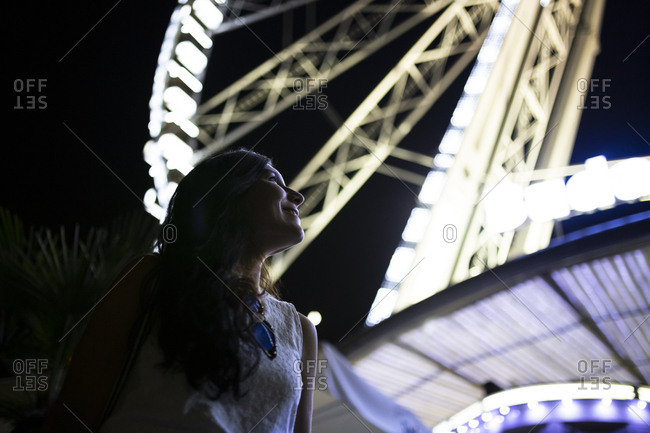 Young woman looking at illuminated noria at night in Budapest, Hungary
