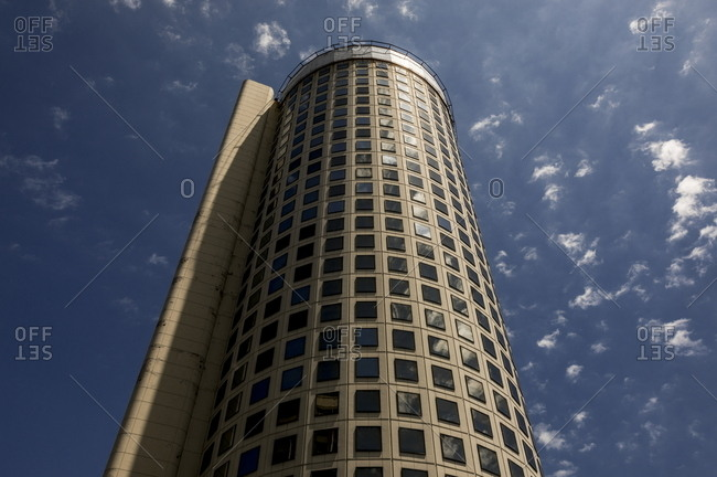 Low angle view of tall round building against blue sky