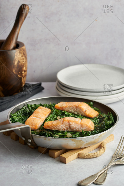 Salmon and kale in skillet
