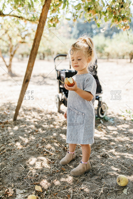 Little girl holding apple with bite out of it and smiling