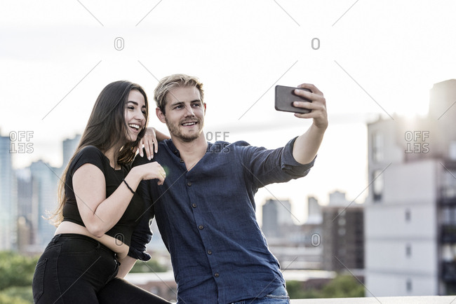 Multiethnic couple taking selfie with mobile phone on building terrace in city