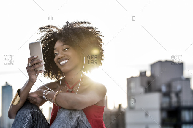 Smiling woman listening to music with earphones on smartphone against city during sunset