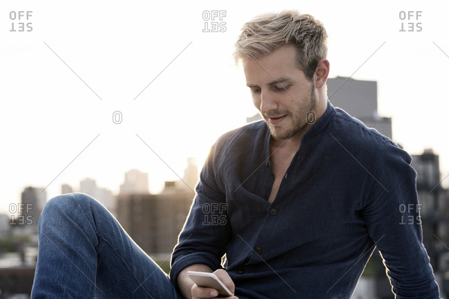 Handsome young man using social media app on smartphone against city