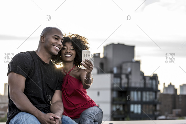 Smiling couple taking selfie with mobile phone on building terrace during sunset