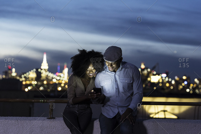 Loving couple sharing mobile phone while leaning on terrace railing in city at night