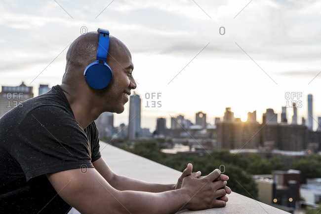 Smiling bald man listening to music on wireless headphones while leaning on terrace railing in city during sunset